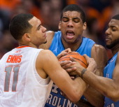 Tyler Ennis of the Syracuse Orange battles with James Michael McAdoo and Leslie McDonald of the North Carolina Tar Heels for a loose ball in the...