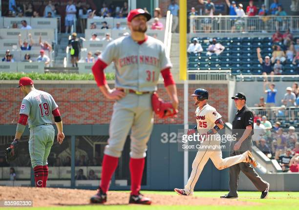 Tyler Flowers of the Atlanta Braves rounds the bases after hitting a fifth inning grand slam as Drew Storen and Joey Votto of the Cincinnati Reds...