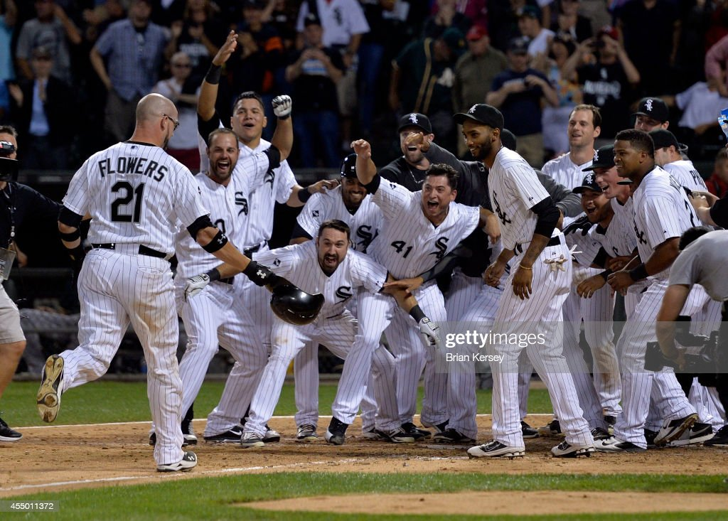 Tyler Flowers of the Chicago White Sox heads home as his teammates wait for him after he hit a gamewinning solo home run during the twelfth inning...