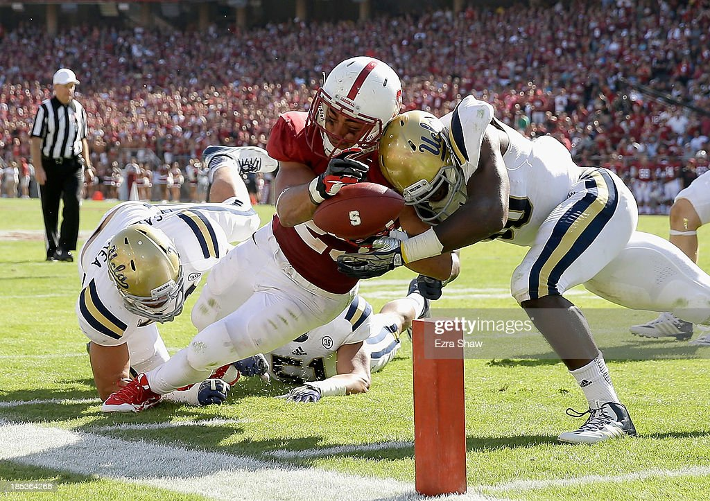 Tyler Gaffney #25 of the Stanford Cardinal is hit by Myles Jack #30 of the UCLA Bruins as he dives for the endzone at Stanford Stadium on October 19, 2013 in Palo Alto, California. The ball was marked on the 1-yard line and the Cardinal scored later in the drive.