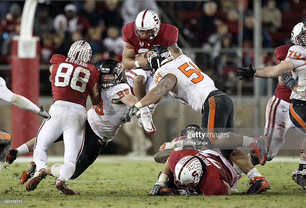 Tyler Gaffney #25 of the Stanford Cardinal jumps in the air as he is hit by Stephen Paea #54 and Gabe Miller #99 of the Oregon State Beavers at Stanford Stadium on November 27, 2010 in Palo Alto, California.