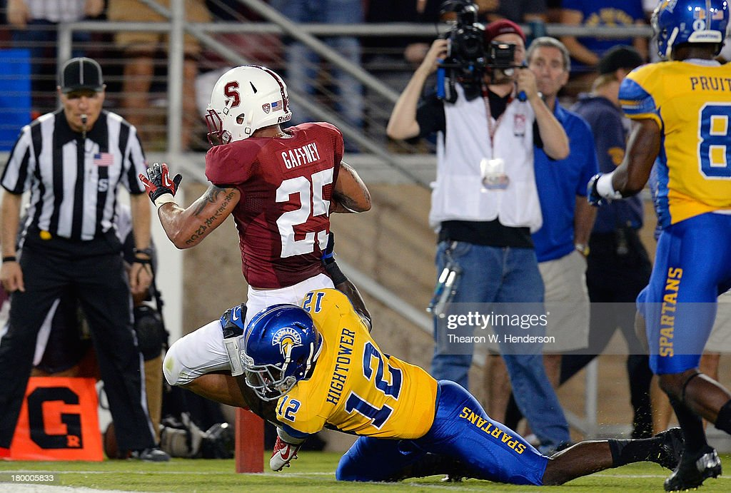 Tyler Gaffney #25 of the Stanford Cardinal scores on a sixteen yard touchdown run dragging Forrest Hightower #12 of the San Jose State Spartans into the endzone during the second quarter at Stanford Stadium on September 7, 2013 in Palo Alto, California.
