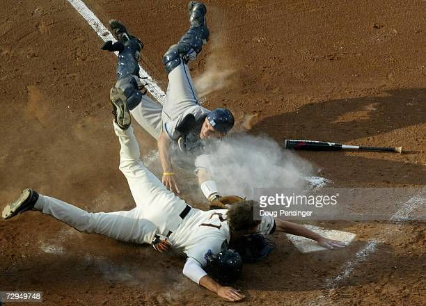 Tyler Graham of the Oregon State Beavers is safe at home ahead of a late tag by catcher Benji Johnson of the North Carolina Tar Heels as he scored...