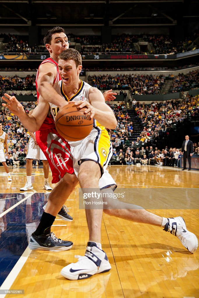 <a gi-track='captionPersonalityLinkClicked' href=/galleries/search?phrase=Tyler+Hansbrough&family=editorial&specificpeople=642794 ng-click='$event.stopPropagation()'>Tyler Hansbrough</a> #50 of the Indiana Pacers drives against <a gi-track='captionPersonalityLinkClicked' href=/galleries/search?phrase=Carlos+Delfino&family=editorial&specificpeople=206625 ng-click='$event.stopPropagation()'>Carlos Delfino</a> #10 of the Houston Rockets on January 18, 2013 at Bankers Life Fieldhouse in Indianapolis, Indiana.