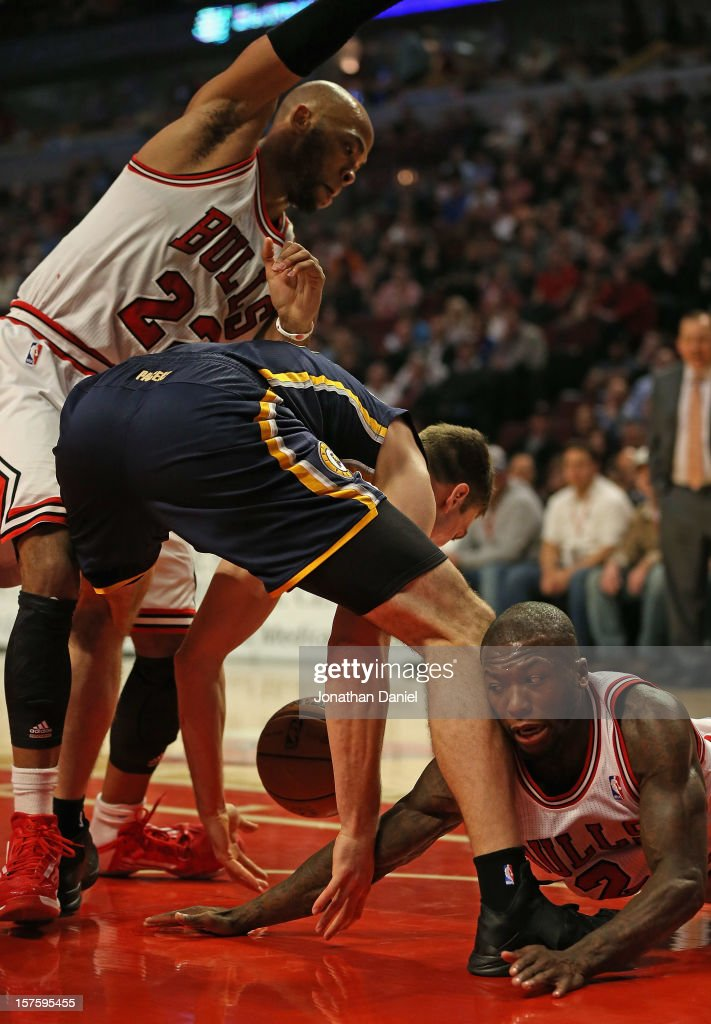 <a gi-track='captionPersonalityLinkClicked' href=/galleries/search?phrase=Tyler+Hansbrough&family=editorial&specificpeople=642794 ng-click='$event.stopPropagation()'>Tyler Hansbrough</a> #50 of the Indiana Pacers losses control of the ball under pressure from <a gi-track='captionPersonalityLinkClicked' href=/galleries/search?phrase=Taj+Gibson&family=editorial&specificpeople=4029461 ng-click='$event.stopPropagation()'>Taj Gibson</a> #22 and <a gi-track='captionPersonalityLinkClicked' href=/galleries/search?phrase=Nate+Robinson&family=editorial&specificpeople=208906 ng-click='$event.stopPropagation()'>Nate Robinson</a> #2 of the Chicago Bulls as he tries to drive to the lane at the United Center on December 4, 2012 in Chicago, Illinois.