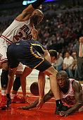Tyler Hansbrough of the Indiana Pacers losses control of the ball under pressure from Taj Gibson and Nate Robinson of the Chicago Bulls as he tries...