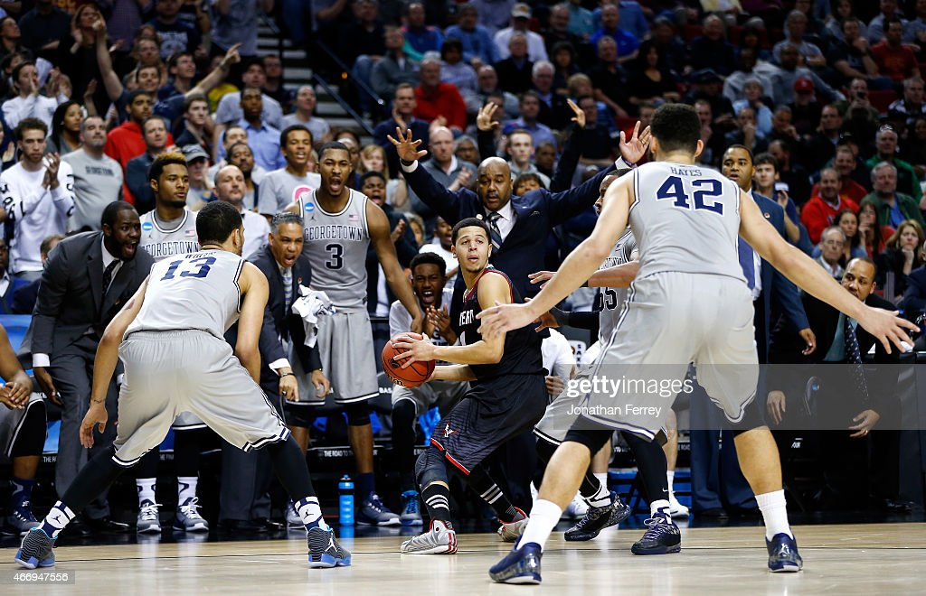 Tyler Harvey of the Eastern Washington Eagles looks to pass against Paul White and Bradley Hayes of the Georgetown Hoyas as head coach John Thompson...