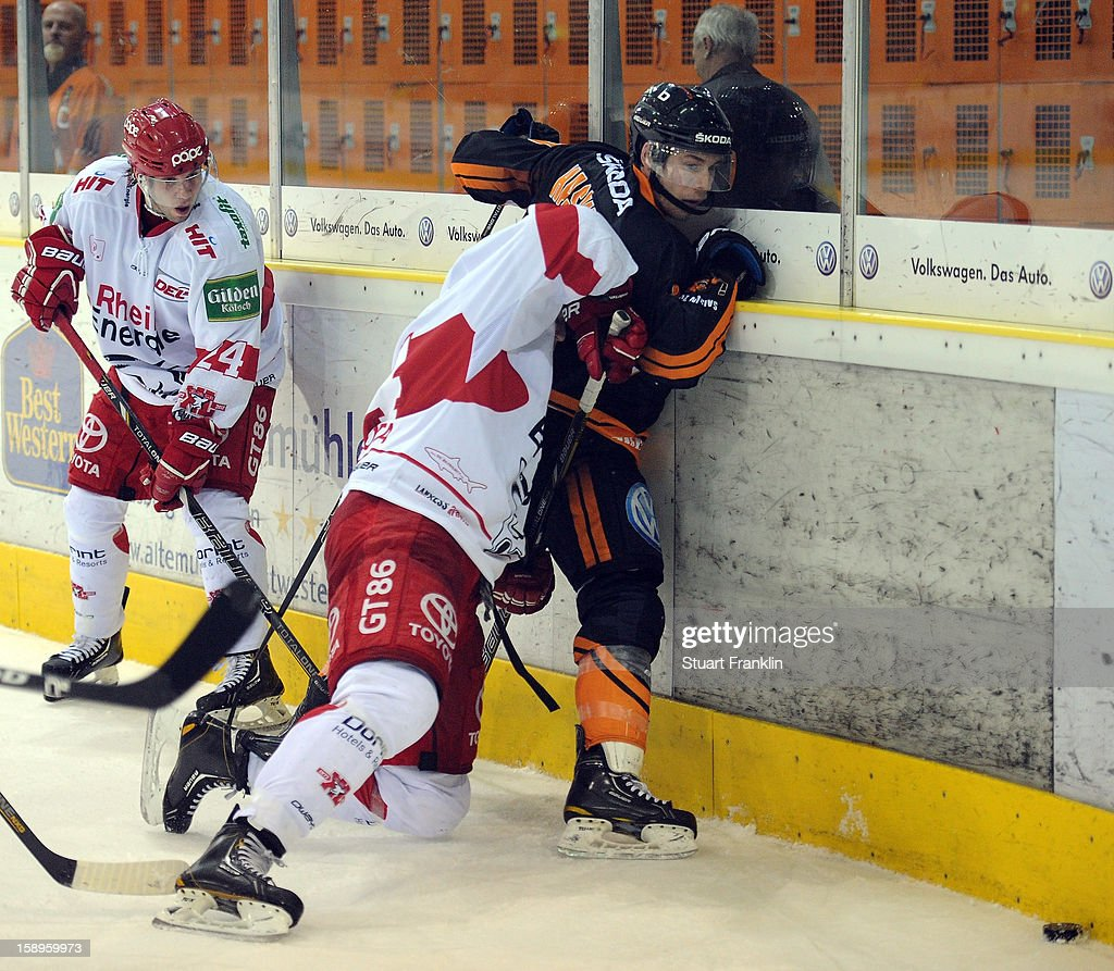 Tyler Haskin of Wolfsburg challenges for the puck with Bjorn Krupp of Cologne during the DEL match between Grizzly Adams Wolfsburg and Kolner Haie at the Volksbank BraWo Eisarena on January 4, 2013 in Wolfsburg, Germany