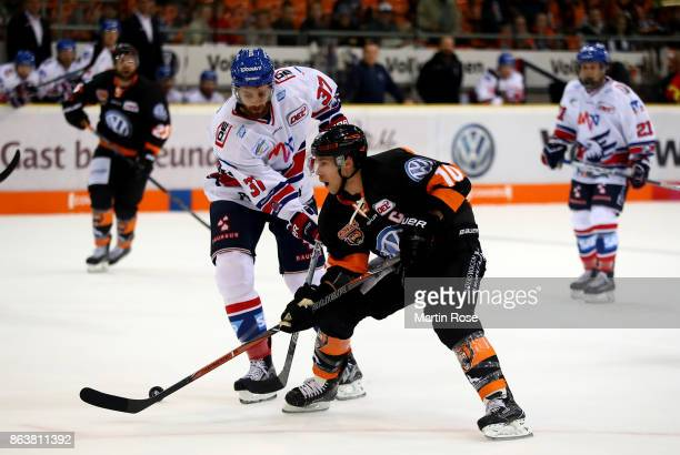 Tyler Haskins of Wolfsburg and Thomas Larkin of Mannheim battle for the puck during the DEL match between Grizzlys Wolfsburg and Adler Mannheim at...