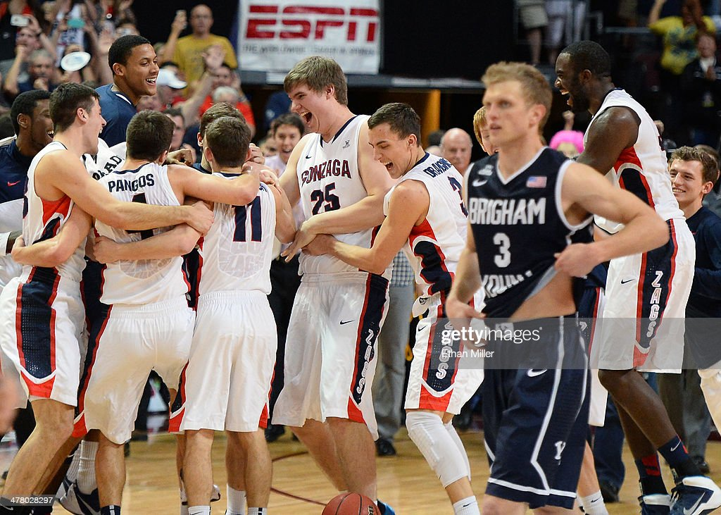 Tyler Haws #3 of the Brigham Young Cougars walks off the court as members of the Gonzaga Bulldogs celebrate after winning the championship game of the West Coast Conference Basketball tournament 75-64 over the Cougars at the Orleans Arena on March 11, 2014 in Las Vegas, Nevada.
