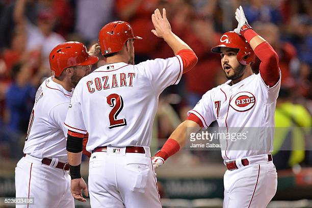 Tyler Holt of the Cincinnati Reds and Zack Cozart of the Cincinnati Reds congratulate Eugenio Suarez of the Cincinnati Reds at home plate after...