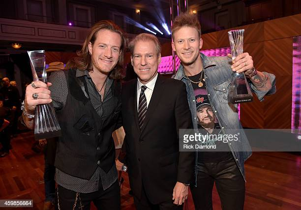Tyler Hubbard of Florida Georgia Line CMT's John Hamlin and Brian Kelley of Florida Georgia Line attend the 2014 CMT Artists Of The Year at the...