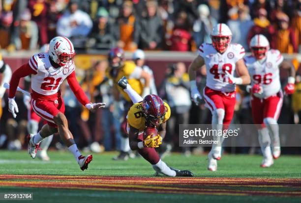 Tyler Johnson of the Minnesota Golden Gophers trips while carrying the ball in the second quarter against the Nebraska Cornhuskers at TCF Bank...