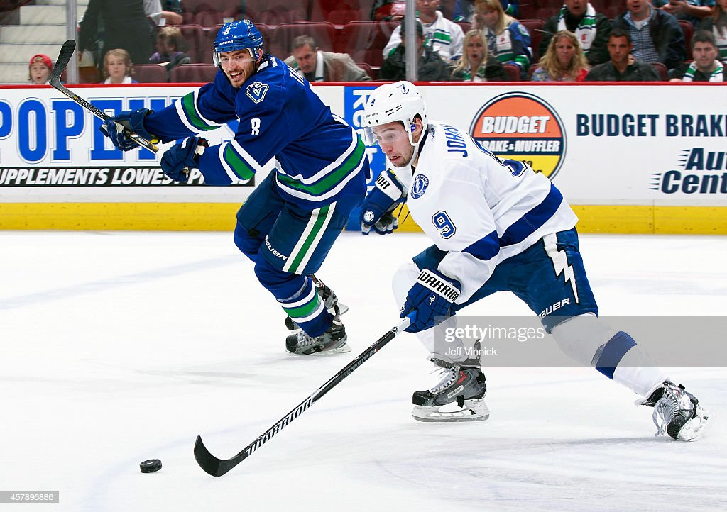 Tyler Johnson #9 of the Tampa Bay Lightning and Christopher Tanev #8 of the Vancouver Canucks skate up ice during their NHL game at Rogers Arena October 18, 2014 in Vancouver, British Columbia, Canada.