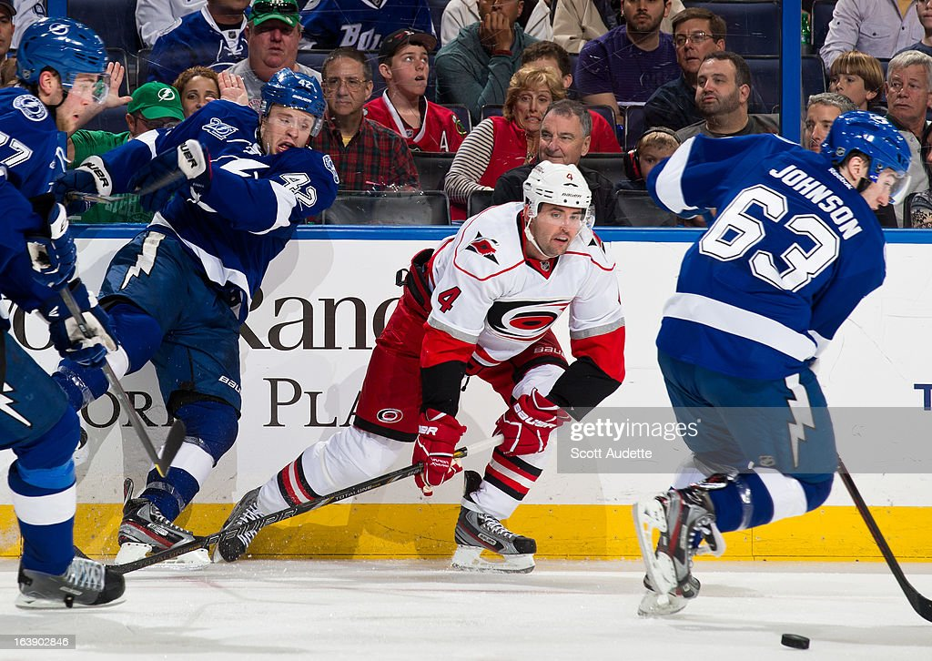Tyler Johnson #63 of the Tampa Bay Lightning and Jamie McBain #4 of the Carolina Hurricanes fight for control of the puck during the second period of the game at the Tampa Bay Times Forum on March 16, 2013 in Tampa, Florida.
