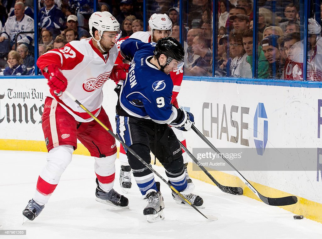 <a gi-track='captionPersonalityLinkClicked' href=/galleries/search?phrase=Tyler+Johnson+-+Ice+Hockey+Player&family=editorial&specificpeople=14574766 ng-click='$event.stopPropagation()'>Tyler Johnson</a> #9 of the Tampa Bay Lightning controls the puck against <a gi-track='captionPersonalityLinkClicked' href=/galleries/search?phrase=Kyle+Quincey&family=editorial&specificpeople=2234340 ng-click='$event.stopPropagation()'>Kyle Quincey</a> #27 and <a gi-track='captionPersonalityLinkClicked' href=/galleries/search?phrase=Henrik+Zetterberg&family=editorial&specificpeople=201520 ng-click='$event.stopPropagation()'>Henrik Zetterberg</a> #40 of the Detroit Red Wings during the third period at the Tampa Bay Times Forum on February 8, 2014 in Tampa, Florida.