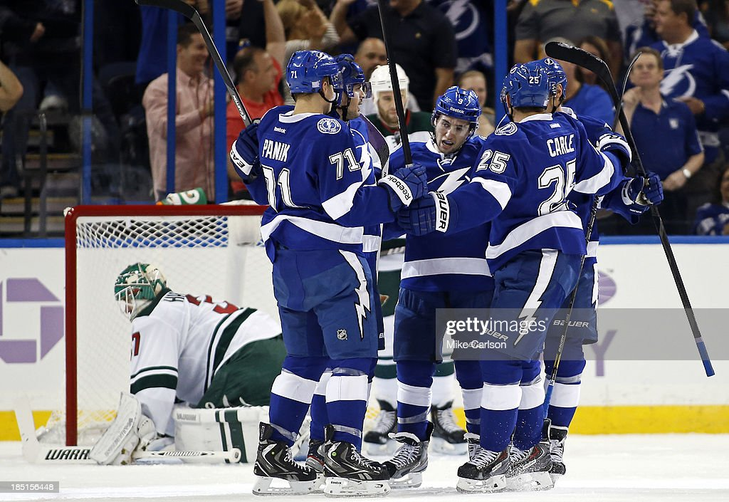 <a gi-track='captionPersonalityLinkClicked' href=/galleries/search?phrase=Tyler+Johnson+-+Ice+Hockey+Player&family=editorial&specificpeople=14574766 ng-click='$event.stopPropagation()'>Tyler Johnson</a> #9 of the Tampa Bay Lightning (C) is congratulated on his goal by teammates, including Richard Panik #71 and <a gi-track='captionPersonalityLinkClicked' href=/galleries/search?phrase=Matt+Carle&family=editorial&specificpeople=582495 ng-click='$event.stopPropagation()'>Matt Carle</a> #25 in front of goalie <a gi-track='captionPersonalityLinkClicked' href=/galleries/search?phrase=Josh+Harding&family=editorial&specificpeople=700587 ng-click='$event.stopPropagation()'>Josh Harding</a> #37 of the Minnesota Wild at the Tampa Bay Times Forum on October 17, 2013 in Tampa, Florida.