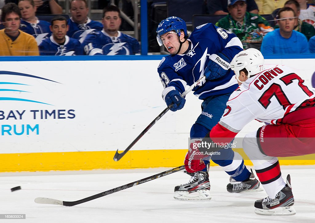 <a gi-track='captionPersonalityLinkClicked' href=/galleries/search?phrase=Tyler+Johnson+-+Ice+Hockey+Player&family=editorial&specificpeople=14574766 ng-click='$event.stopPropagation()'>Tyler Johnson</a> #63 of the Tampa Bay Lightning shoots the puck while guarded by <a gi-track='captionPersonalityLinkClicked' href=/galleries/search?phrase=Joe+Corvo&family=editorial&specificpeople=206339 ng-click='$event.stopPropagation()'>Joe Corvo</a> #77 of the Carolina Hurricanes during the first period of the game at the Tampa Bay Times Forum on March 16, 2013 in Tampa, Florida.