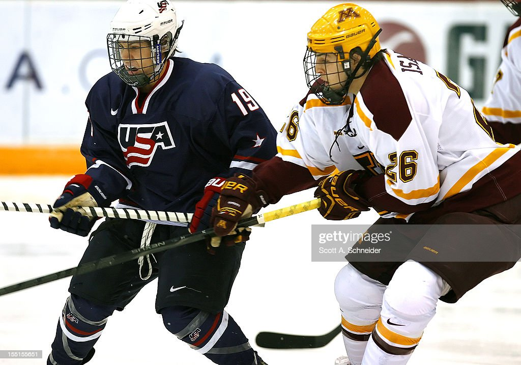 Tyler Kelleher #19 of United States U-18 battles for the puck with Christian Isackson #26 of the University of Minnesota October 26, 2012 at Mariucci Arena in Minneapolis, Minnesota.