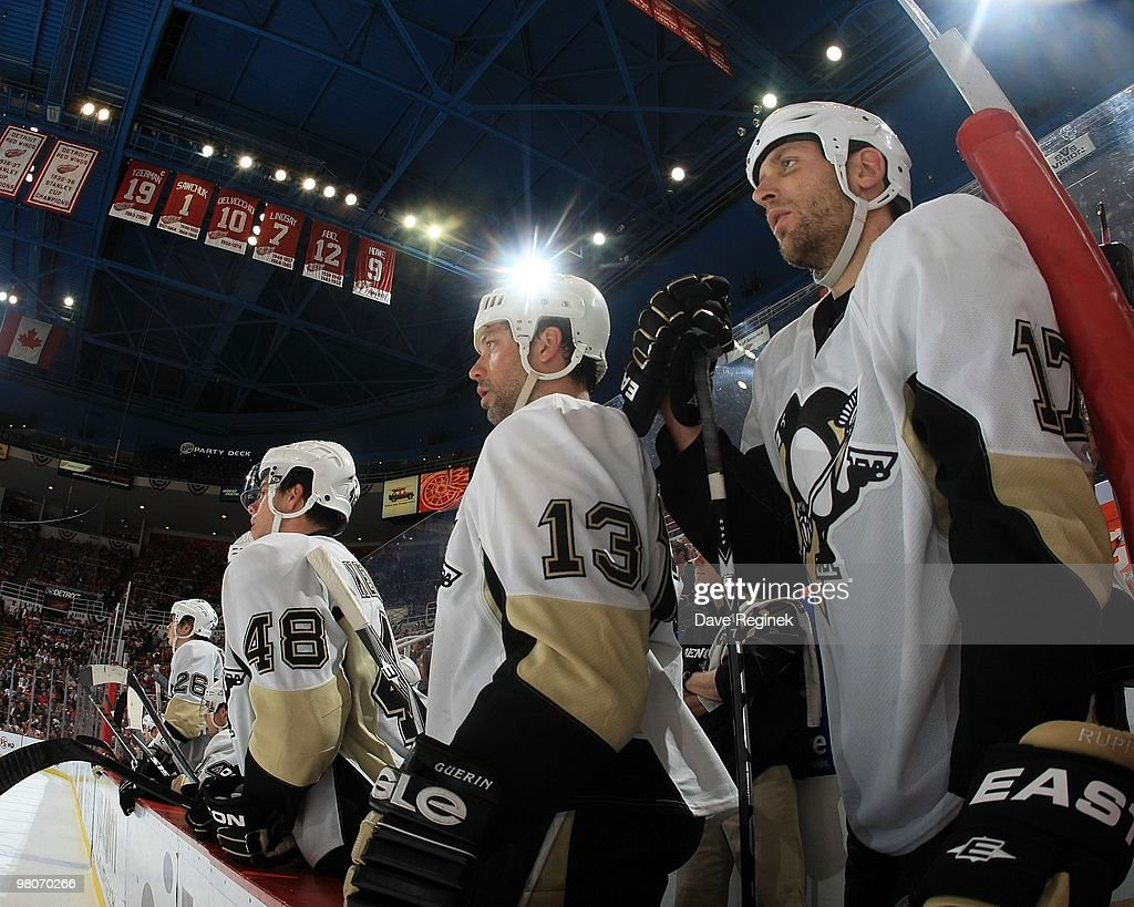 Tyler Kennedy Bill Guerin and Michael Rupp of the Pittsburgh Penguins watch the play from the bench during an NHL game against the Detroit Red Wings...