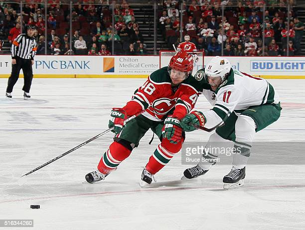 Tyler Kennedy of the New Jersey Devils is checked by Zach Parise of the Minnesota Wild at the Prudential Center on March 17 2016 in Newark New Jersey...