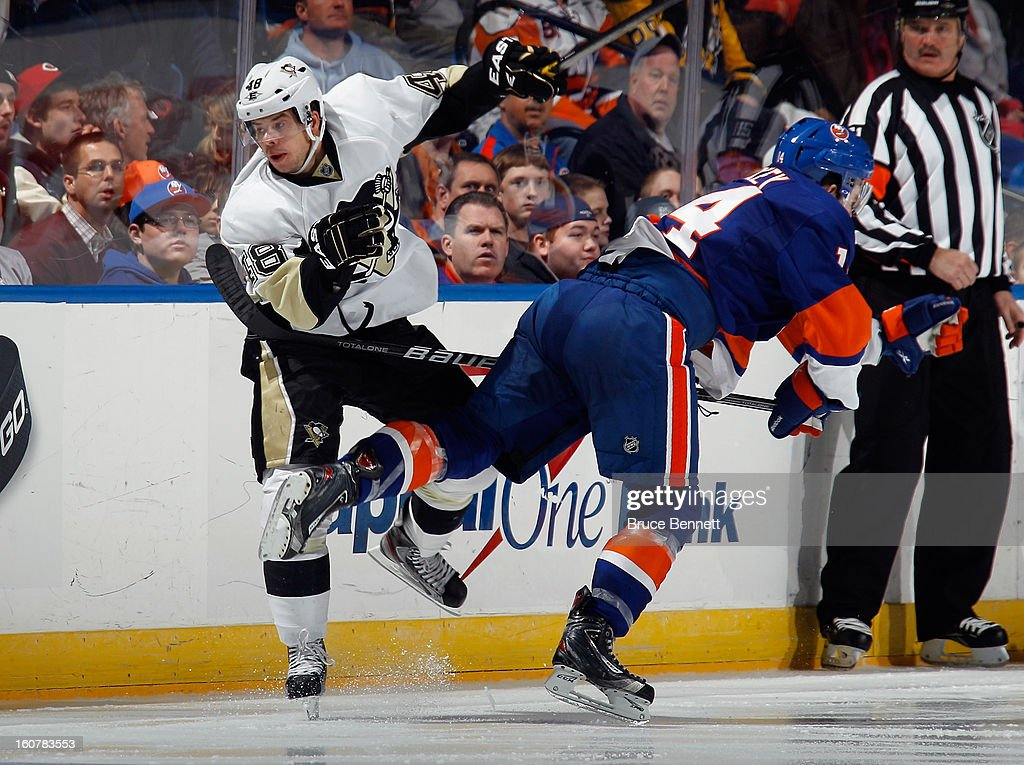 Tyler Kennedy #48 of the Pittsburgh Penguins hits Thomas Hickey #14 of the New York Islanders during the third period at the Nassau Veterans Memorial Coliseum on February 5, 2013 in Uniondale, New York. The Penguins defeated the Islanders 4-2.