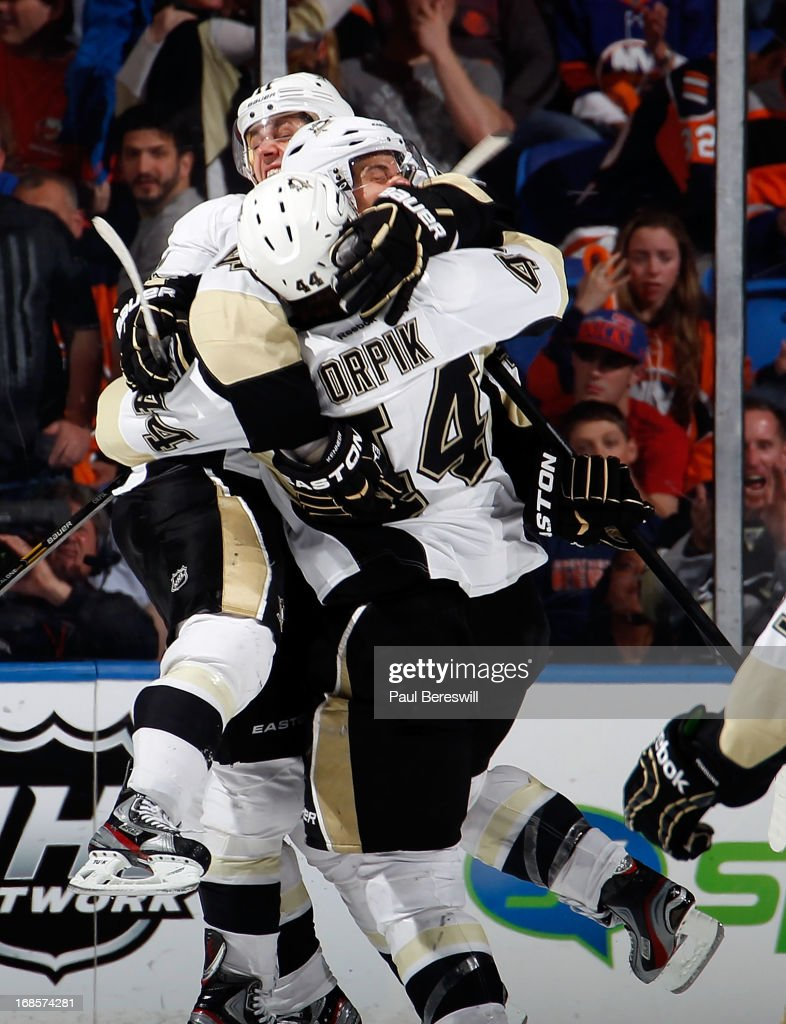 Tyler Kennedy #48 of the Pittsburgh Penguins leaps into the arms of <a gi-track='captionPersonalityLinkClicked' href=/galleries/search?phrase=Brooks+Orpik&family=editorial&specificpeople=213074 ng-click='$event.stopPropagation()'>Brooks Orpik</a> #44 of the Penguins as Orpik just scored the game winning goal in overtime in Game Six of the Eastern Conference Quarterfinals to eliminate the New York Islanders from the playoffs during the 2013 NHL Stanley Cup Playoffs at Nassau Veterans Memorial Coliseum on May 11, 2013 in Uniondale, New York. Penguins won 4-3 in overtime.
