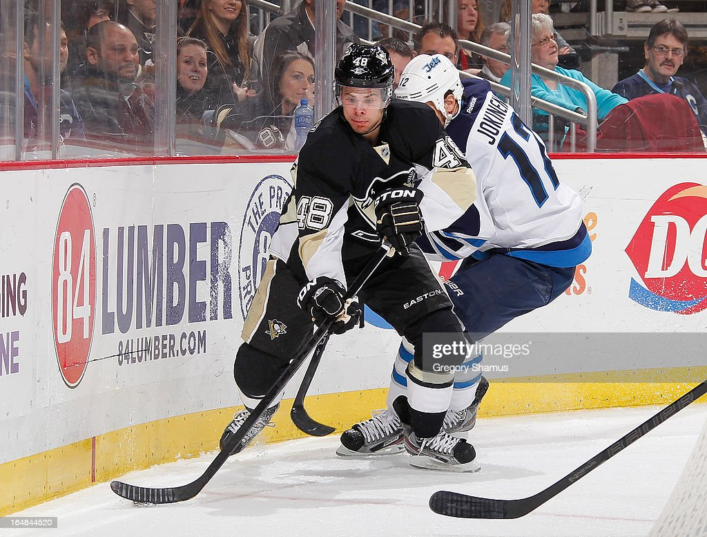 <a gi-track='captionPersonalityLinkClicked' href=/galleries/search?phrase=Tyler+Kennedy&family=editorial&specificpeople=2119414 ng-click='$event.stopPropagation()'>Tyler Kennedy</a> #48 of the Pittsburgh Penguins skates past the defense of <a gi-track='captionPersonalityLinkClicked' href=/galleries/search?phrase=Olli+Jokinen&family=editorial&specificpeople=202946 ng-click='$event.stopPropagation()'>Olli Jokinen</a> #12 of the Winnipeg Jets on March 28, 2013 at Consol Energy Center in Pittsburgh, Pennsylvania. Pittsburgh won the game 4-0.