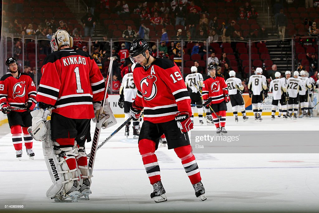 Tyler Kennedy #48,Keith Kinkaid #1 and Travis Zajac #19 of the New Jersey Devils skate off the ice as the Pittsburgh Penguins celebrate the win on March 6, 2016 at Prudential Center in Newark, New Jersey.The Pittsburgh Penguins defeated the New Jersey Devils 6-1.