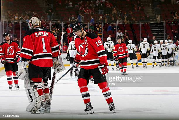 Tyler KennedyKeith Kinkaid and Travis Zajac of the New Jersey Devils skate off the ice as the Pittsburgh Penguins celebrate the win on March 6 2016...