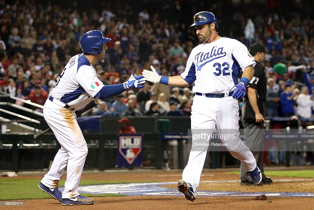Tyler LaTorre #32 of Italy celebrates with teammate Nick Punto #8 after scoring a run in the second inning against Team USA during the World Baseball Classic First Round Group D game at Chase Field on March 9, 2013 in Phoenix, Arizona.