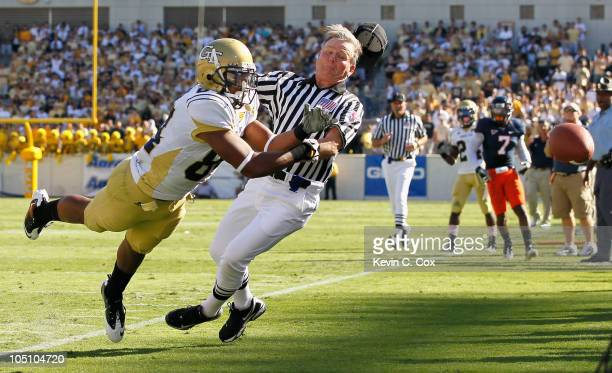 Tyler Melton of the Georgia Tech Yellow Jackets collides with field judge Billy Beckett as he fails to pull in this reception against the Virginia...
