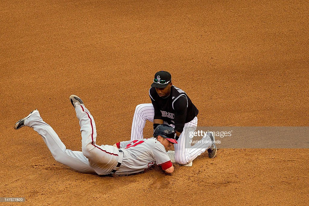 Tyler Moore of the Washington Nationals is picked off of second base by Jonathan Herrera of the Colorado Rockies during the fourth inning at Coors...