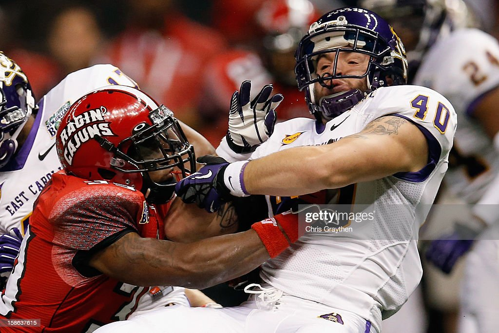 Tyler Morvant #39 of the Louisiana-Lafayette Ragin Cajuns tackles Hunter Furr #40 of the East Carolina Pirates during the R+L Carriers New Orleans Bow at the Mercedes-Benz Superdome on December 22, 2012 in New Orleans, Louisiana.