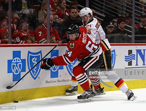 Tyler Motte of the Chicago Blackhawks battles for the puck with Jyrki Jokipakka of the Calgary Flames at the United Center on November 1 2016 in...
