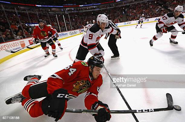 Tyler Motte of the Chicago Blackhawks hits the ice as he knocks the puck away from Taylor Hall of the New Jersey Devils at the United Center on...