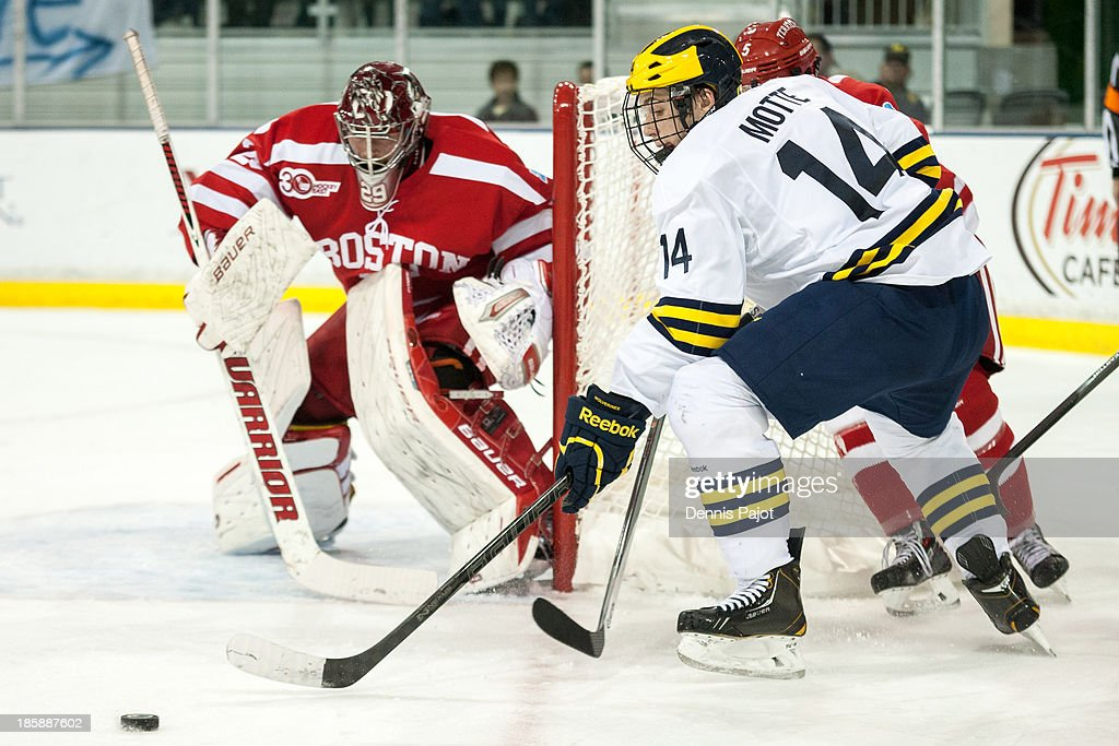 Tyler Motte #14 of the Michigan Wolverines moves the puck against Matt O'Connor #29 of the Boston University Terriers on October 25, 2013 at Yost Ice Arena in Ann Arbor, Michigan.