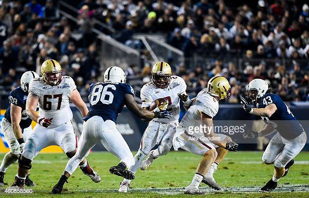 Tyler Murphy of the Boston College Eagles runs around CJ Olaniyan of the Penn State Nittany Lions in the second quarter of the 2014 New Era Pinstripe...