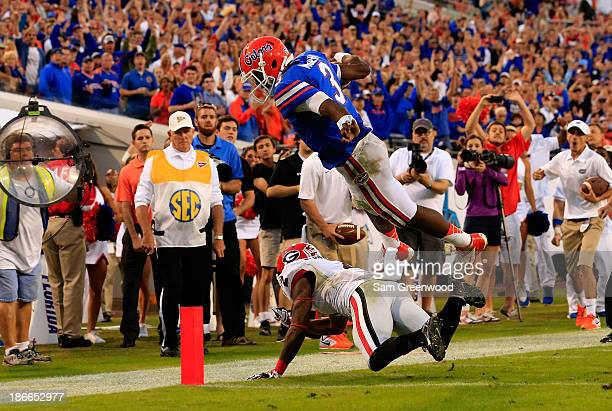 Tyler Murphy of the Florida Gators dives over Sheldon Dawson of the Georgia Bulldogs for a touchdown during the game at EverBank Field on November 2...