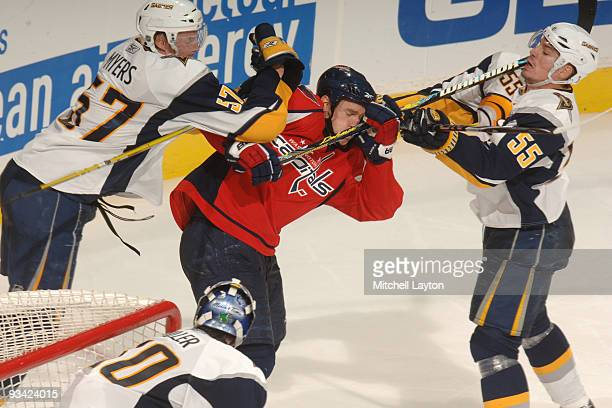 Tyler Myers and Joshen Hecht of the Buffalo Sabres put a hit on Chris Clark of the Washington Capitals during a NHL hockey game on November 25 2009...