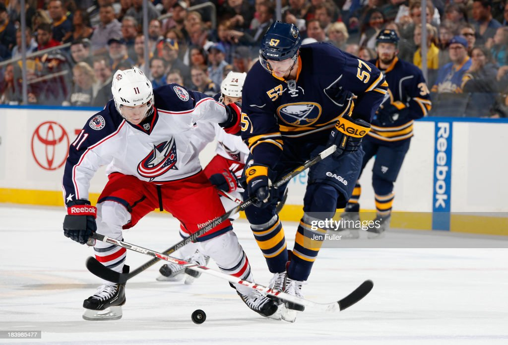 Tyler Myers of the Buffalo Sabres battles for the puck with Matt Calvert of the Columbus Blue Jackets at First Niagara Center on October 10 2013 in...