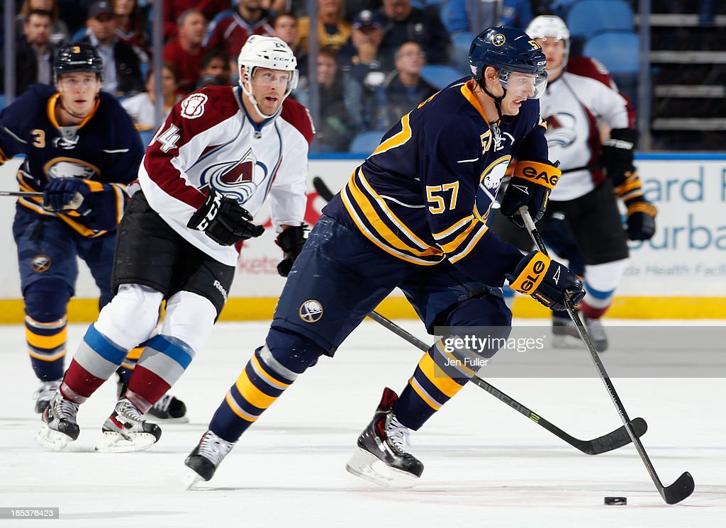 Tyler Myers #57 of the Buffalo Sabres carries the puck in front of Marc-Andre Cliche #24 of the Colorado Avalanche at First Niagara Center on October 19, 2013 in Buffalo, New York. Colorado defeated Buffalo 4-2.