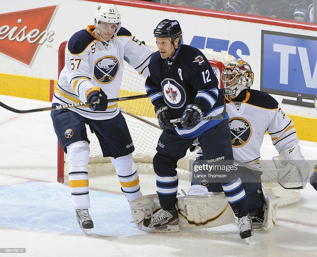 Tyler Myers #57 of the Buffalo Sabres checks Olli Jokinen #12 of the Winnipeg Jets in front of goaltender Ryan Miller #30 during second period action at the MTS Centre on April 9, 2013 in Winnipeg, Manitoba, Canada. The Jets defeated the Sabres 4-1.