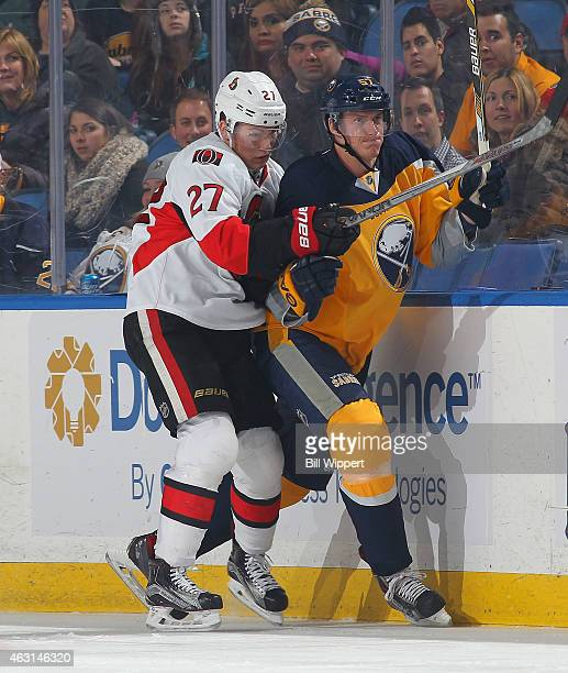 Tyler Myers of the Buffalo Sabres gets checked against the boards by Curtis Lazar of the Ottawa Senators on February 10 2015 at the First Niagara...
