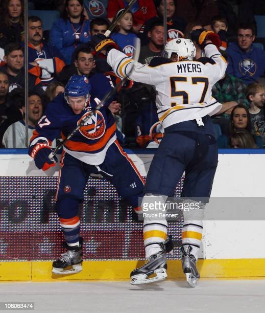 Tyler Myers of the Buffalo Sabres hits Andrew MacDonald of the New York Islanders at the Nassau Coliseum on January 15 2011 in Uniondale New York The...