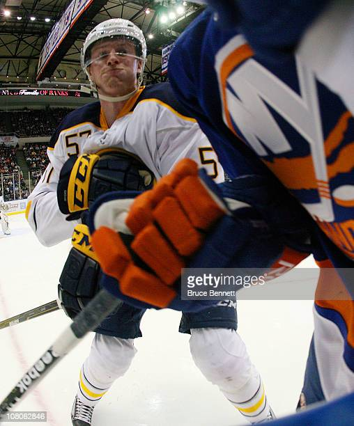 Tyler Myers of the Buffalo Sabres moves in to hit a New York Islander at the Nassau Coliseum on January 15 2011 in Uniondale New York
