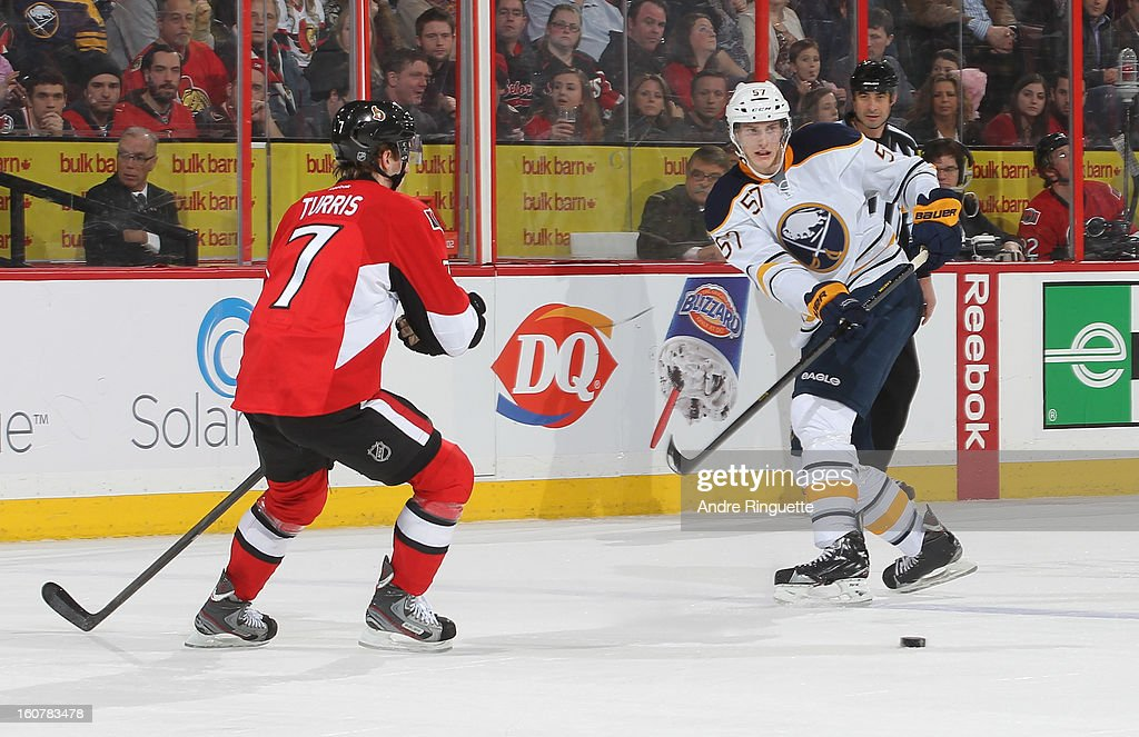 Tyler Myers #57 of the Buffalo Sabres passes the puck against Kyle Turris #7 of the Ottawa Senators on February 5, 2013 at Scotiabank Place in Ottawa, Ontario, Canada.