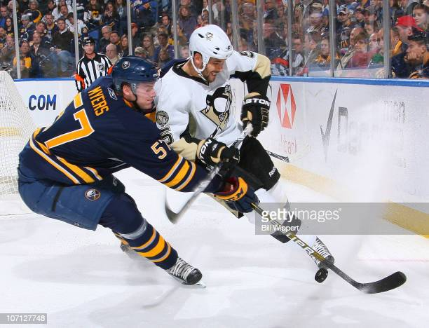Tyler Myers of the Buffalo Sabres reaches in for the puck against Deryk Engelland of the Pittsburgh Penguins at HSBC Arena on November 24 2010 in...