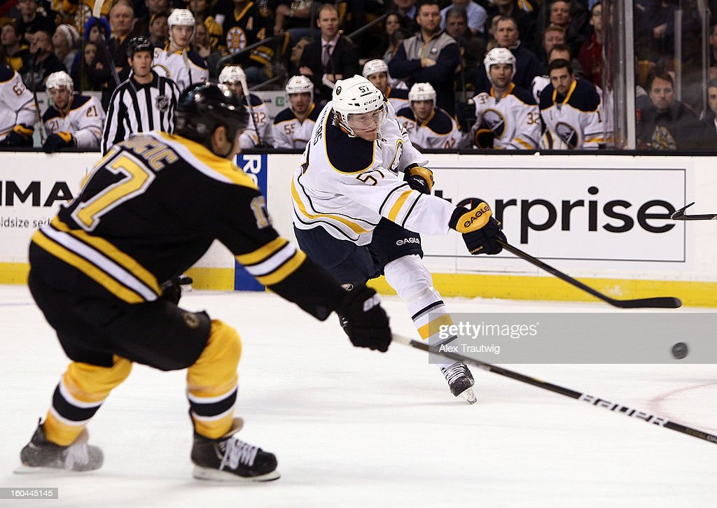 Tyler Myers #57 of the Buffalo Sabres takes a shot as Milan Lucic #17 of the Boston Bruins defends during a game at the TD Garden on January 31, 2013 in Boston, Massachusetts.