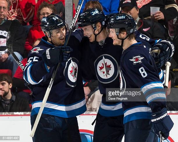 Tyler Myers of the Winnipeg Jets celebrates his goal with teammates Mark Scheifele and Jacob Trouba during the first period of an NHL game against...